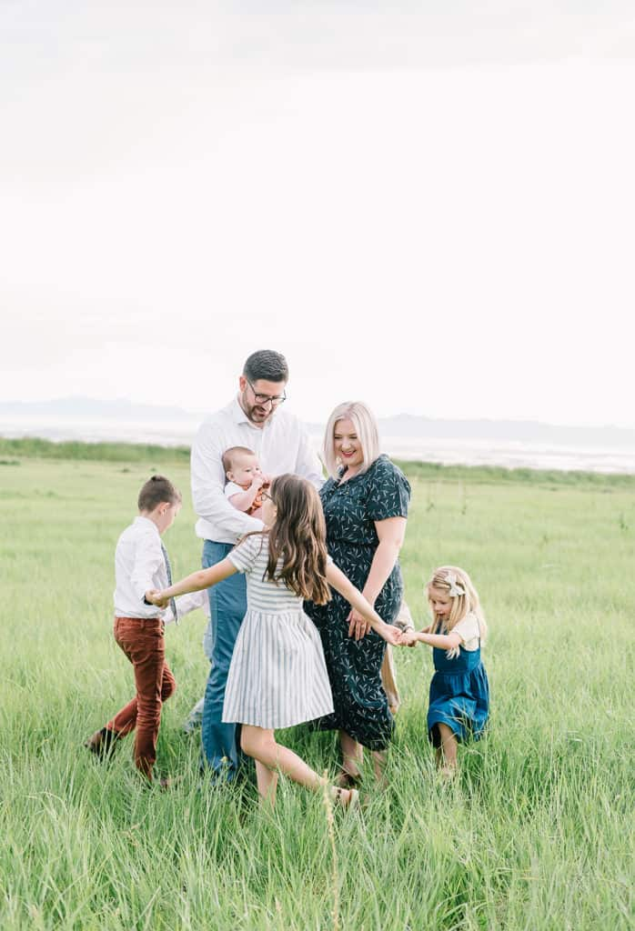 Kids play ring around the rosies around mom and dad, wearing tan, white, blue and rust tones.