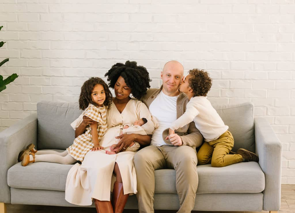Family photo in creams and tans with pop of mustard in lifestyle newborn session.