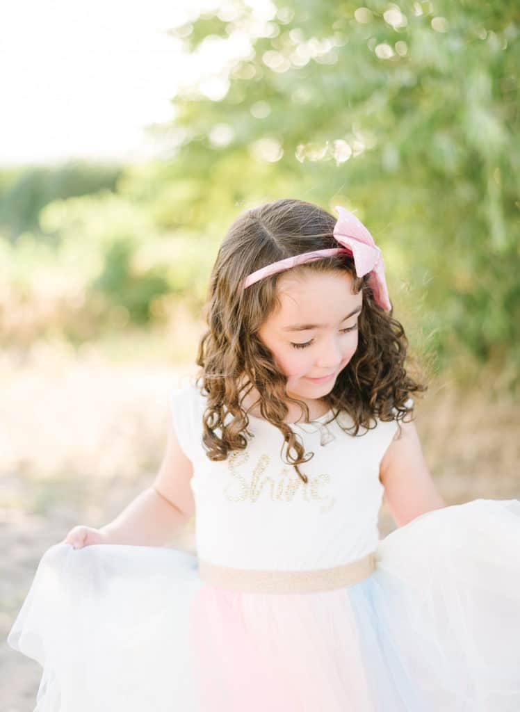 Little girl twirls in pastel dress with gold detailing