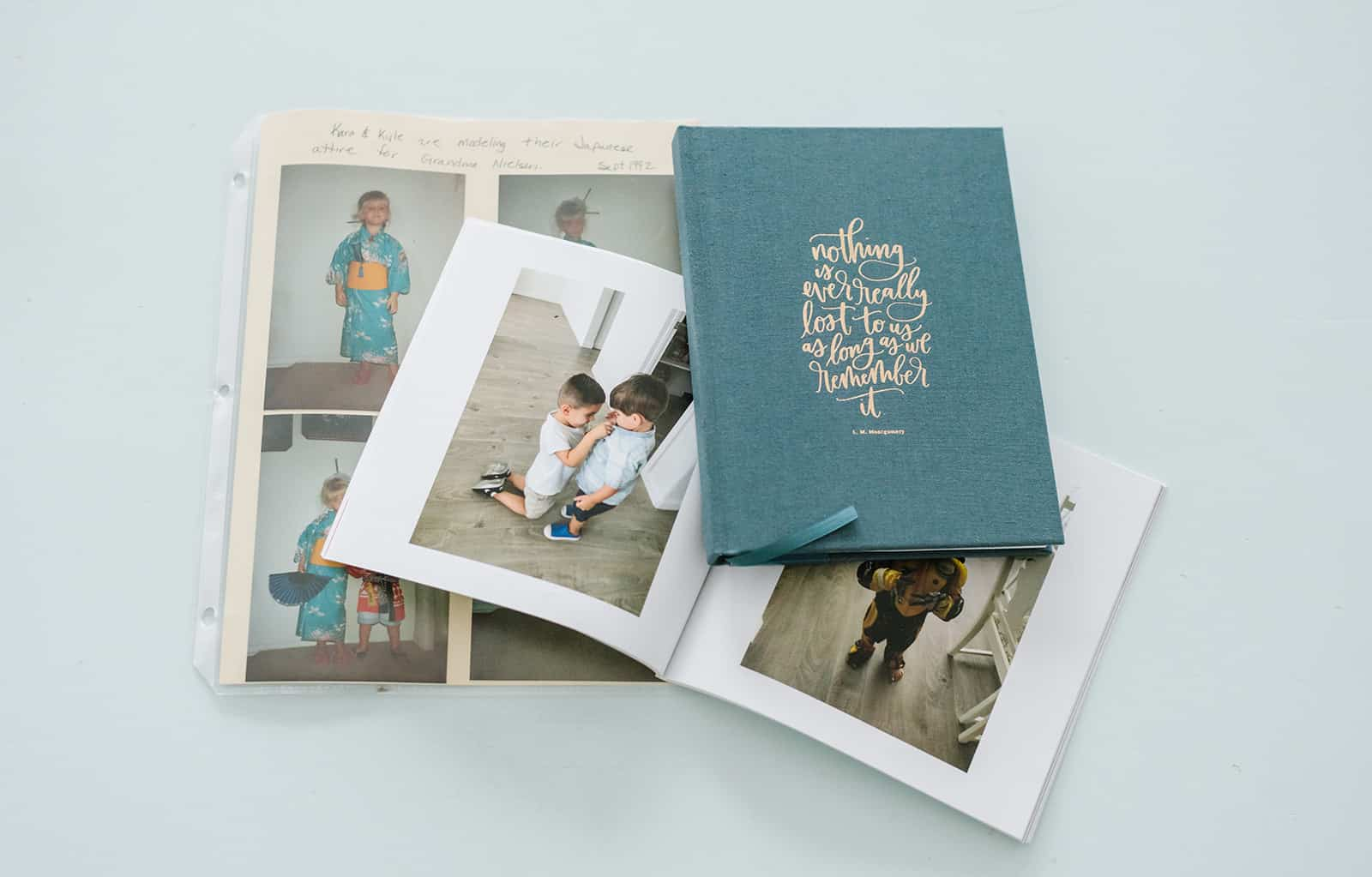 """Scrapbook page, open photobook and onecanoetwo journal with """"nothing is ever really lost to us as long as we remember it"""" quote."""