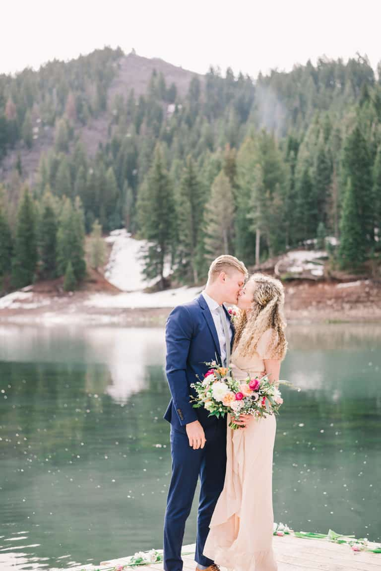 Bride in blush dress kisses groom in a blue suit for the first time as husband and wife in their outdoor wedding ceremony in Tibble Fork, Utah.