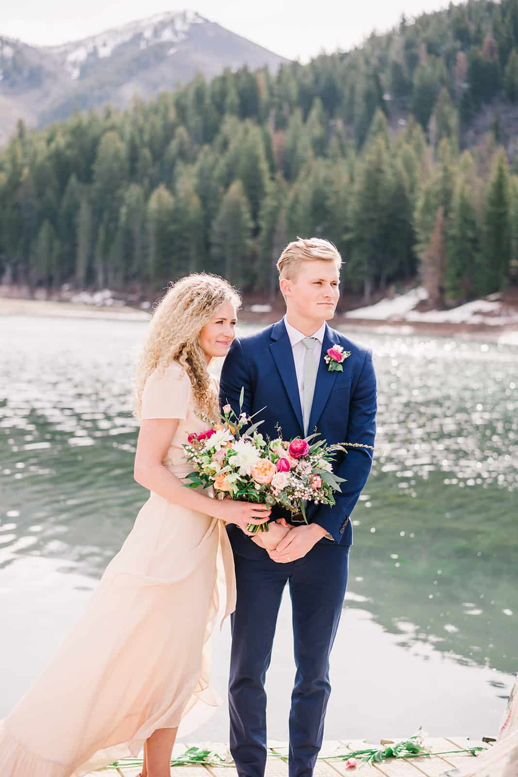 Bride in flowy blush dress holds bouquet with pink, coral and blush flowers. Groom stands next to her in a blue suit in outdoor wedding on the dock at tibble fork, Utah.