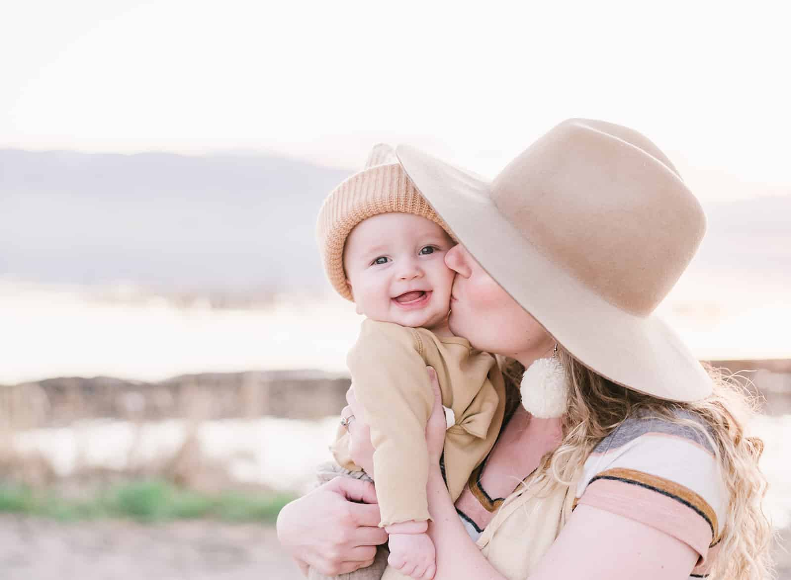 Mom in light brown hat kisses baby in tan front wrap shirt and beanie on vineyard beach during their family pictures.