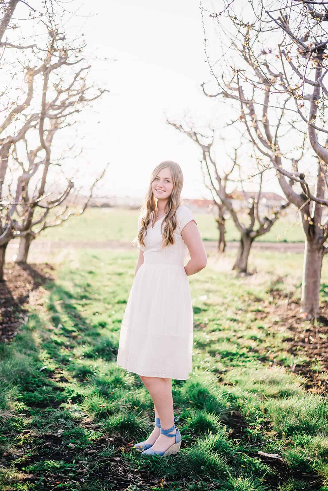 Senior portraits, girl in cream dress poses in front of utah county apple orchard