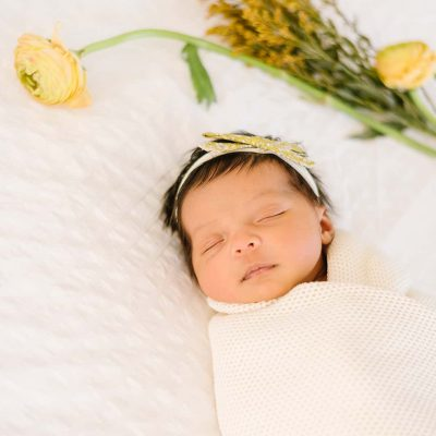 Lifestyle newborn session with fresh flowers white textured backdrop and knit cream swaddle.